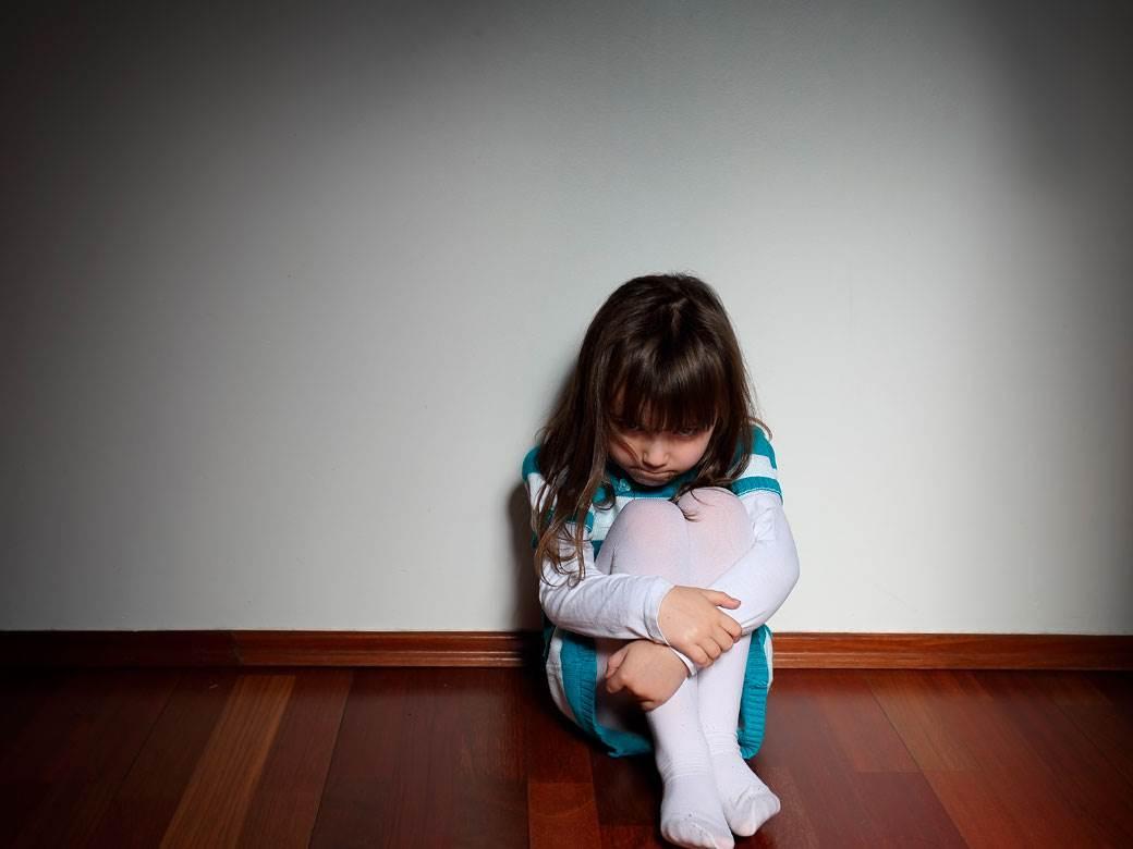 devojčica tužna sedi na podu